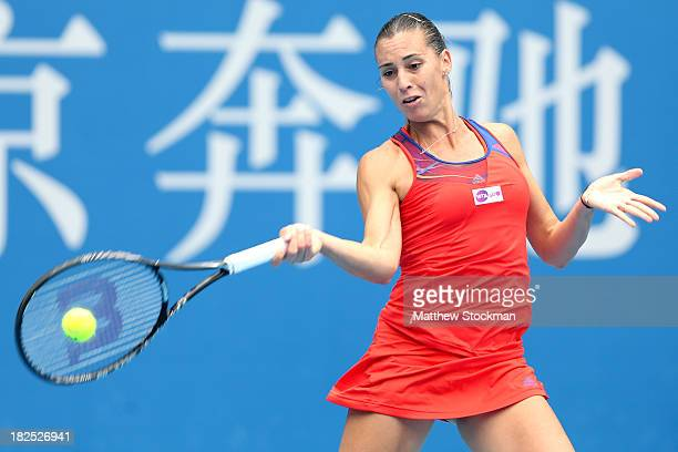 Flavia Pennetta of Italy returns a shot to Ana Ivanovic of Serbia during day three of the 2013 China Open at the National Tennis Center on September...