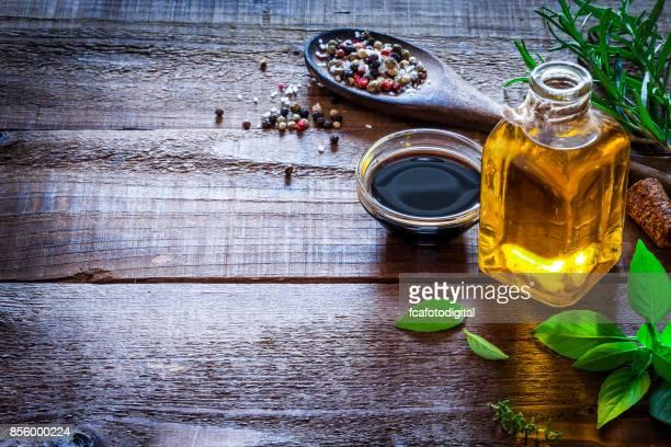 Condimentación: aceite y vinagre en la mesa de madera rústica