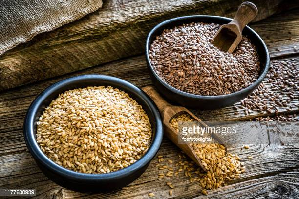 flax seeds in a black bowl on rustic wooden background - flax seed stock pictures, royalty-free photos & images