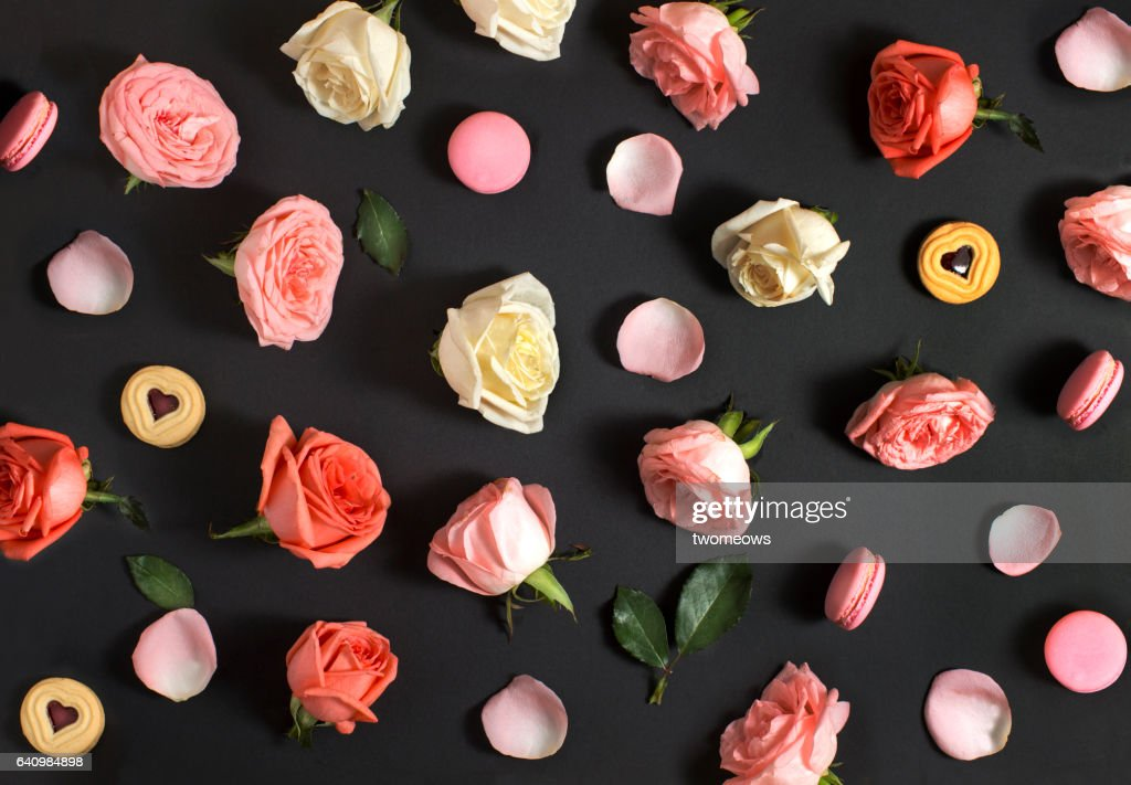 Flay lay roses and macaroon on black background. : Stock Photo