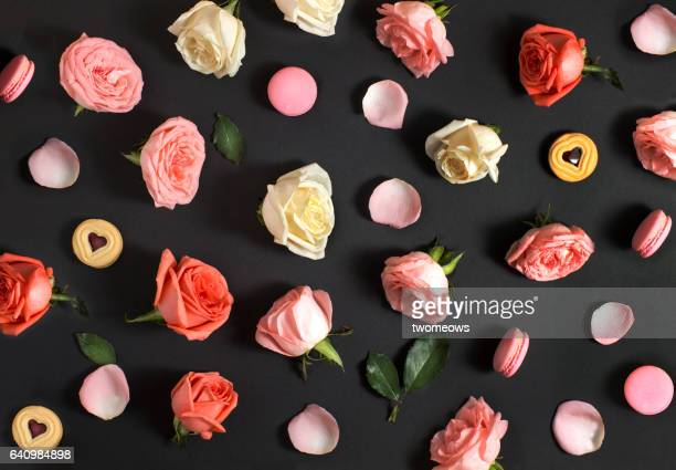 flay lay roses and macaroon on black background. - black rose stock pictures, royalty-free photos & images