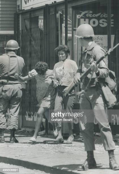 Fleeing the scene Two Negro girls run from a Detroit shop as a national guardsman bayoneted rifle at the ready one of 8000 in the embattled city...