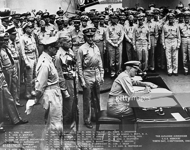 Fleet Admiral Chester Nimitz signs the Japanese surrender document on board the USS Missouri At left are General Douglas MacArthur Admiral William...
