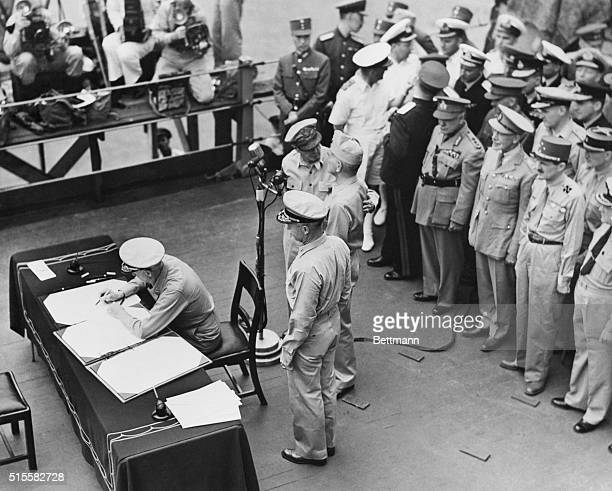 Fleet Admiral Chester W Nimitz signs a treaty with Japan aboard the USS Missouri during official ceremonies for Japan's surrender