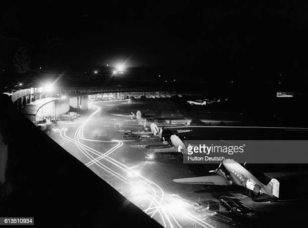 A fleet of Douglas C47 Skytrain cargo planes waits to deliver food supplies during the Berlin Airlift as trucks busily navigate the darkened tarmac