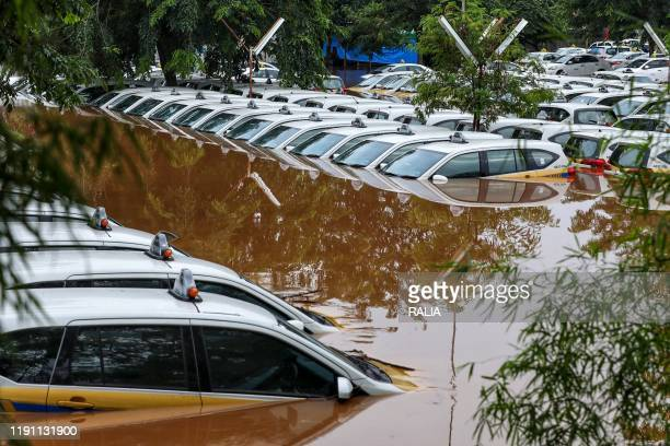 TOPSHOT A fleet of flooded taxis are seen at the operator's submerged parking lot following overnight rain in Jakarta on January 1 2020 Nine people...