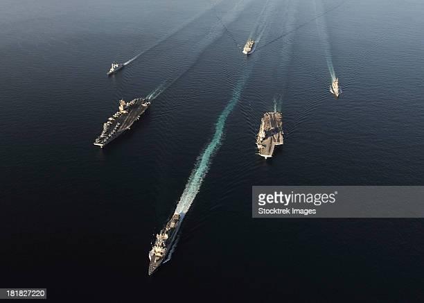 fleet of navy ships transit the arabian sea. - vaisseau de guerre photos et images de collection