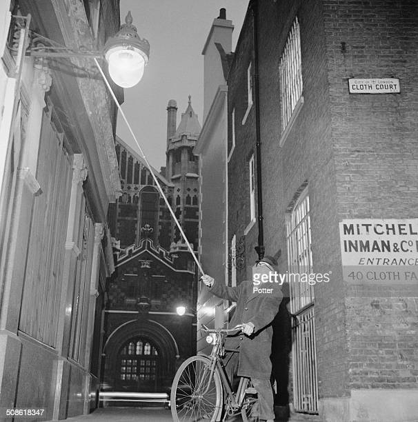 Fleet Street lamp lighter Sid Bee lights a lamp for the last time before his retirement Clerkenwell London 1964