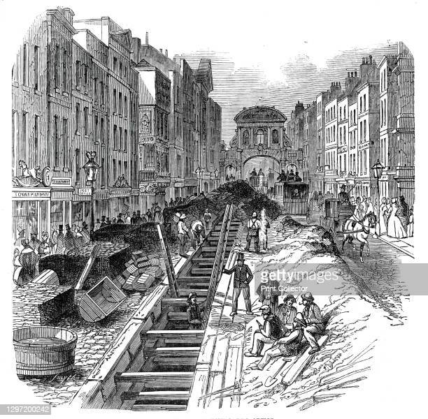 Fleet-Street, deepening the sewer, 1845. Workers improving the underground waste system in London, with Temple Bar in the distance. '...the...