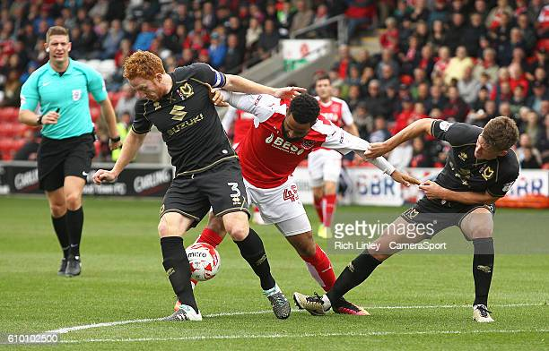Fleetwood Town's Alex Jakubiak battles with Milton Keynes Dons' Dean Lewington and Paul Downing during the Sky Bet League One match between Fleetwood...