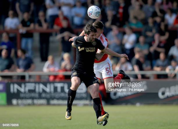 Fleetwood Town's Ashley Eastman and Wigan Athletic's Will Grigg contest a header during the Sky Bet League One match at Highbury Stadium Fleetwood