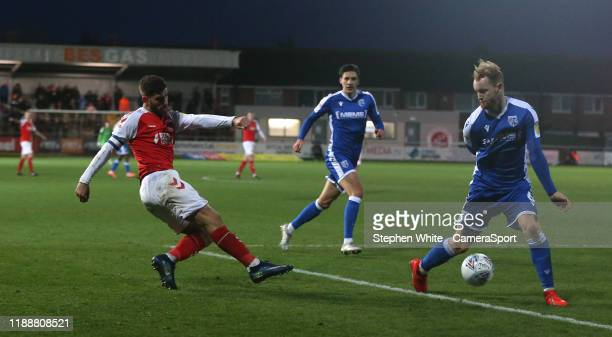 Fleetwood Town's Ched Evans crosses the ball despite the attentions of Gillingham's Connor Ogilvie during the Sky Bet League One match between...