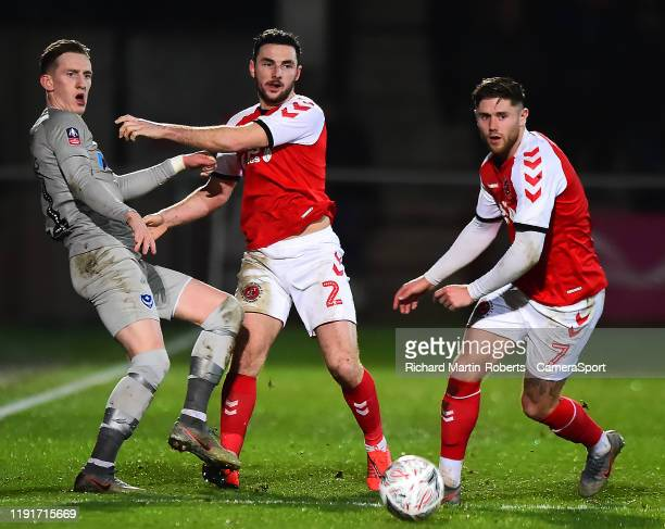 Fleetwood Town's Lewis Coyle and Wes Burns vies for possession with Portsmouth's Ronan Curtis during the FA Cup Third Round match between Fleetwood...