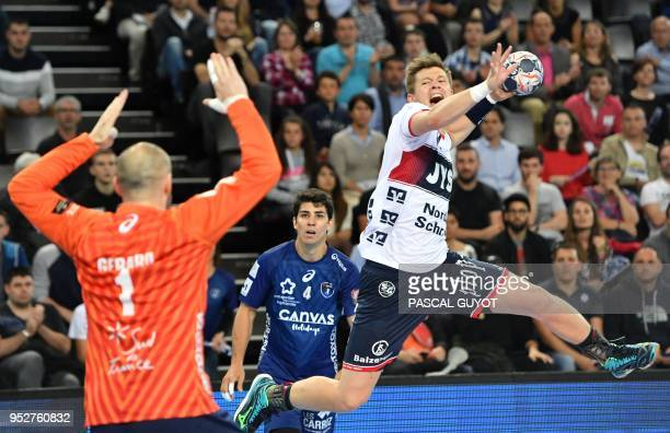 Flensburg's Danish right wing Lasse Svan vies with Montpellier's French goalkeeper Vincent Gerard during the EHF Champions League quarterfinal...