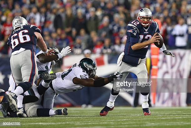 Fletcher Cox of the Philadelphia Eagles attempts to tackle Tom Brady of the New England Patriots during their game at Gillette Stadium on December 6...