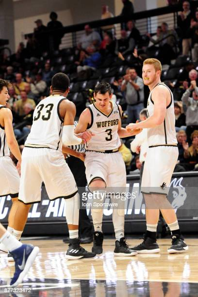 Fletcher Magee guard is congratulated by teammates Cameron Jackson forward and Matthew Pegram center Wofford College Terriers after scoring a...