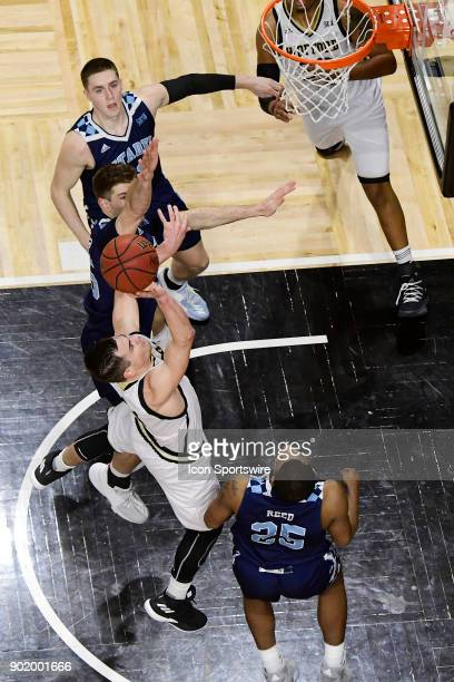 Fletcher Magee guard Wofford College Terriers makes jump shot against Hayden Brown forward Rob Johnson guard =and Alex Reed forward The Citadel...