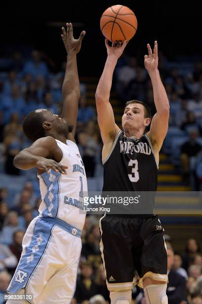 Fletcher Magee of the Wofford Terriers puts up a shot against Theo Pinson of the North Carolina Tar Heels at Dean Smith Center on December 20 2017 in...