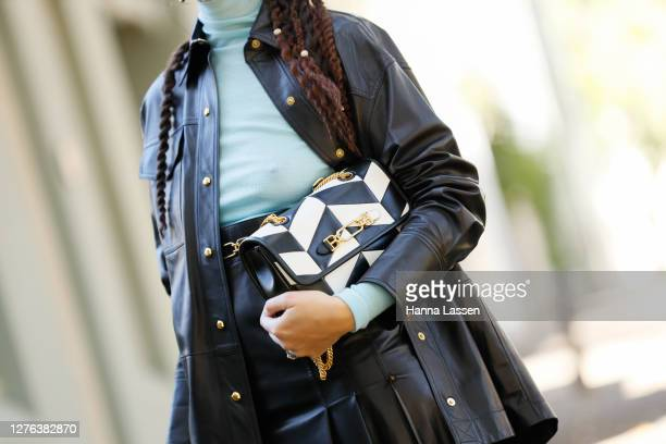 Fleur Egan wearing Bally leather black shirt, skirt with gold button details, black and white bag, beige and black colour blocking boots and blue...