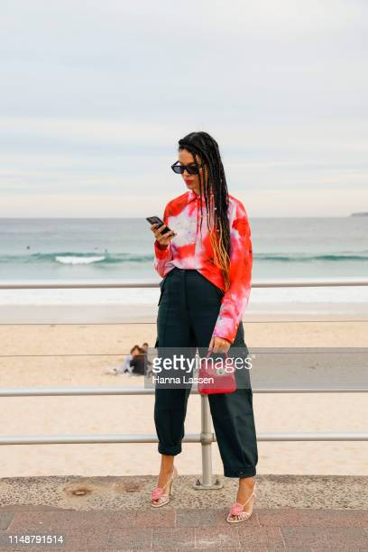 Fleur Egan wearing red shirt dark green pants at MercedesBenz Fashion Week Resort 20 Collections on May 13 2019 in Sydney Australia
