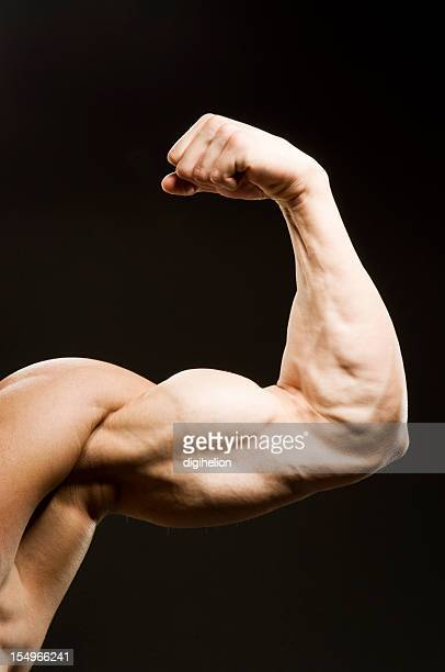 Flexed man's biceps on black background