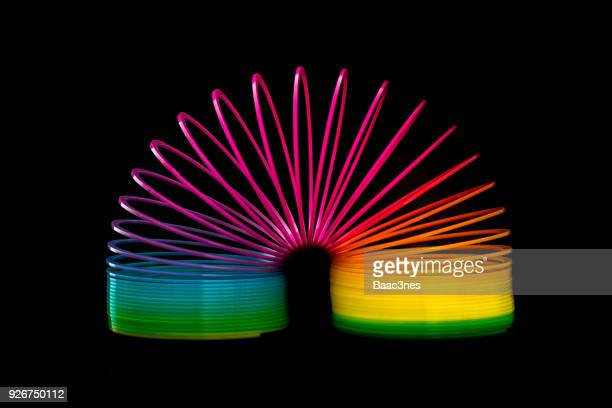 flexibility - colorful slinky toy - metal coil toy stock photos and pictures