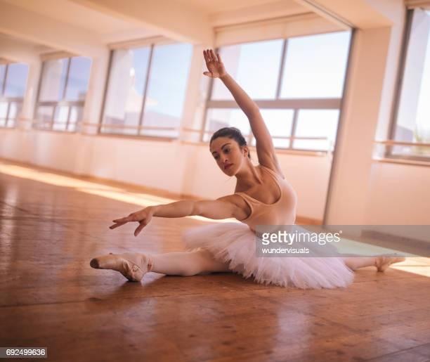 flexibele ballerina doen een kant splitsen tijdens ballet sessie - split acrobatiek stockfoto's en -beelden