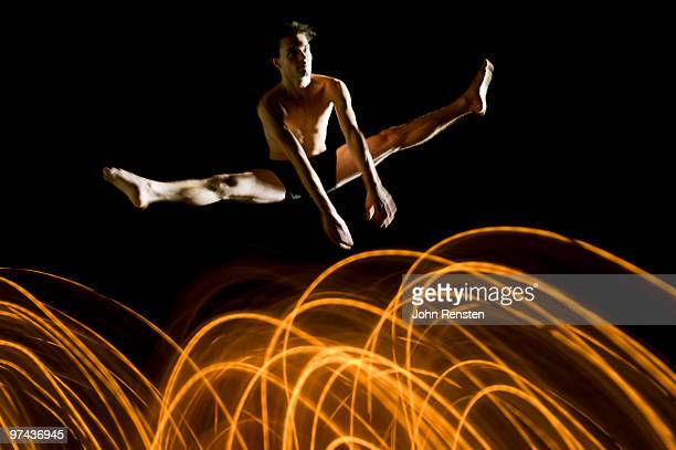 flexible dancer  jumps over abstract light trails
