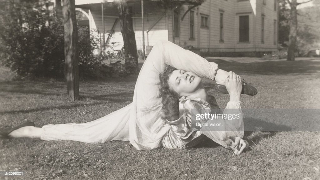 Flexible Woman in a Garden Bending Her Leg Above Her Head : Stock Photo