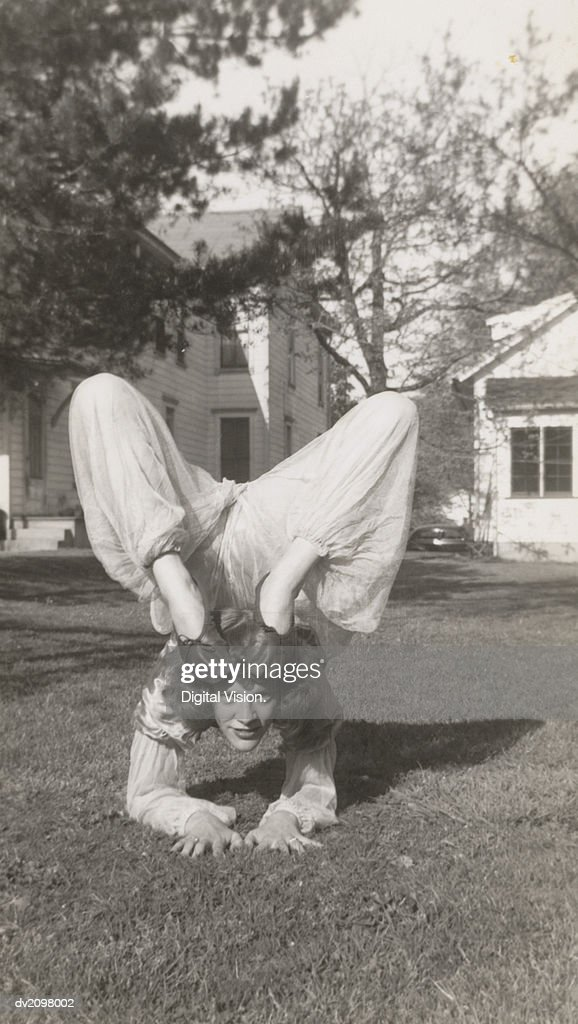 Flexible Woman in a Garden Bending Her Legs Above Her Head : Stock Photo