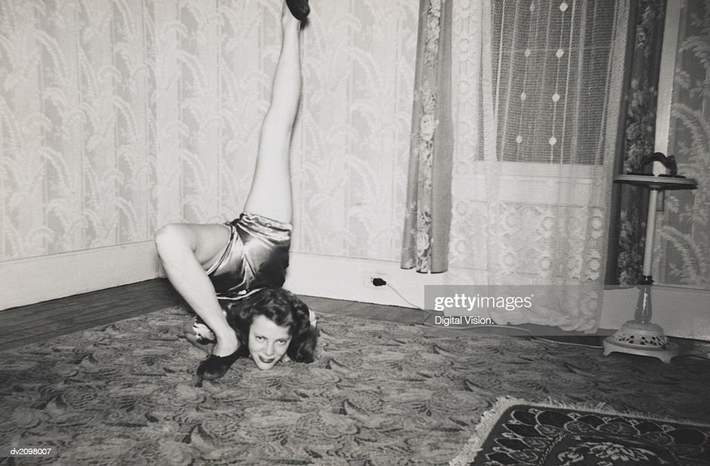 Flexible Woman on the Living Room Floor With Her Leg Over Her Head : Stock Photo