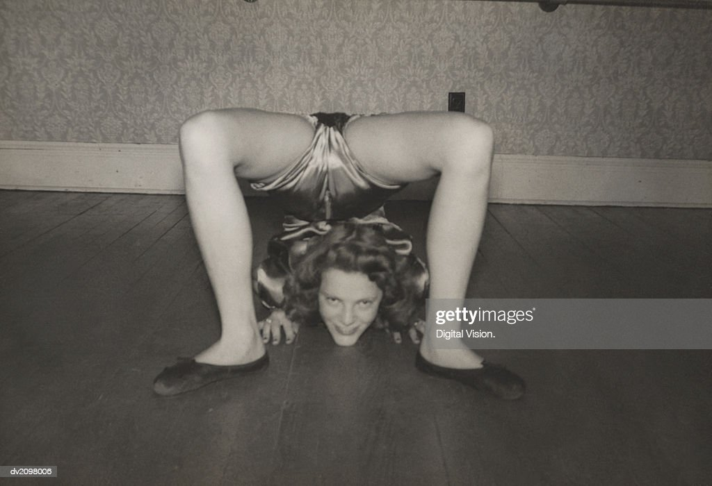 Flexible Woman on the Living Room Floor With Her Legs Over Her Head : Stock Photo