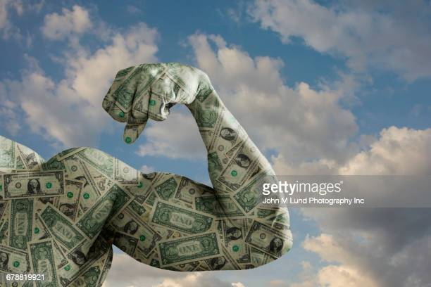 flexing biceps covered with dollars - monetary policy stock pictures, royalty-free photos & images