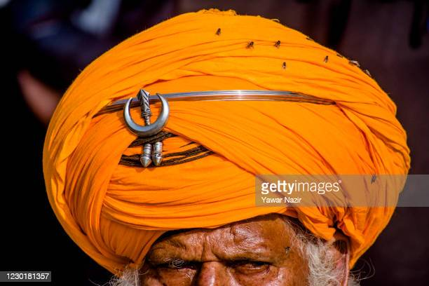 Flies sit on a turban of an Indian farmer as he listen to a speaker on a blocked highway during a protest against the new farm laws on December 17,...