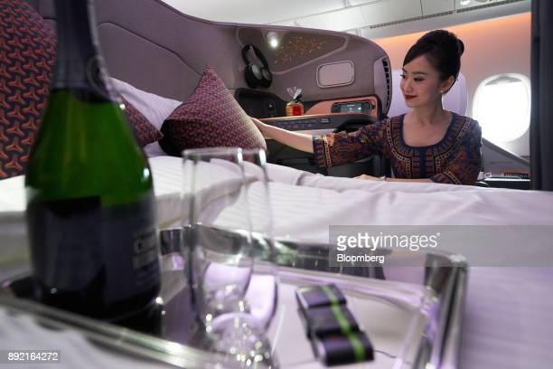 A flight attendant arranges a business class seat of a Singapore Airlines Ltd Airbus SE A380 aircraft with refitted cabins during a media tour at...