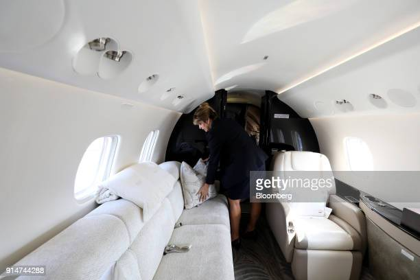 A flight attendant arranges a cushion on a seat inside an Embraer SA Legacy 650E jet during the Singapore Airshow held at the Changi Exhibition...