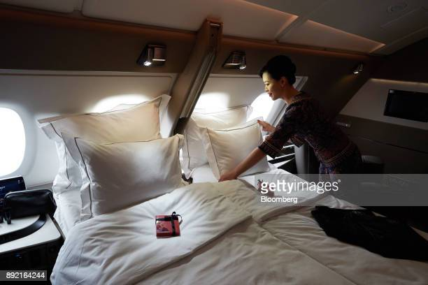 A flight attendant arranges a pillow of a bed in a suite of a Singapore Airlines Ltd Airbus SE A380 aircraft with refitted cabins during a media tour...