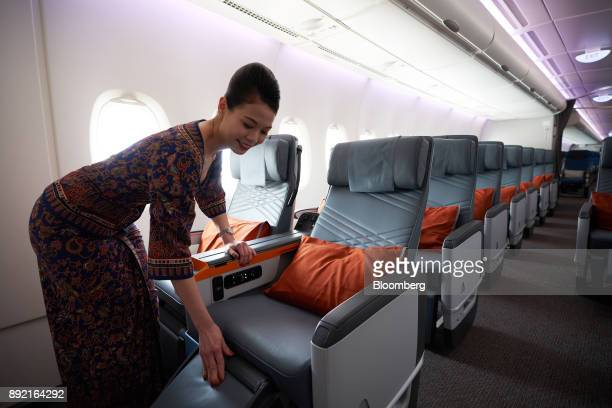 A flight attendant arranges a premium class seat of a Singapore Airlines Ltd Airbus SE A380 aircraft with refitted cabins during a media tour at...