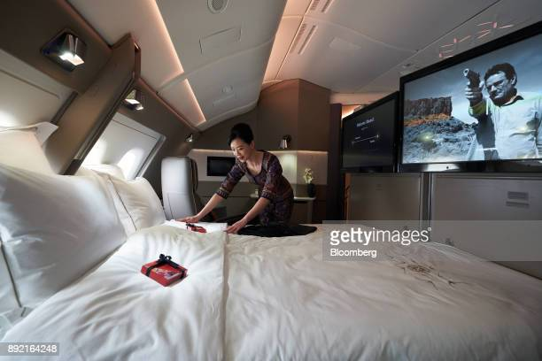 A flight attendant arranges the bed in a suite of a Singapore Airlines Ltd Airbus SE A380 aircraft with refitted cabins during a media tour at Changi...