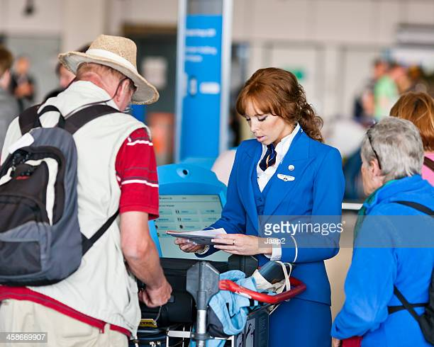 flight attendant assisting at check-in - schiphol airport stock photos and pictures