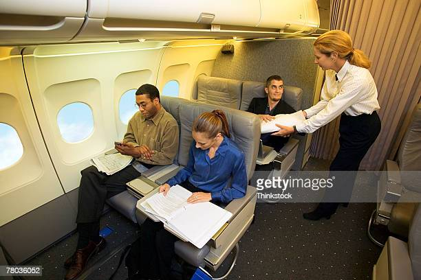 Flight attendant assisting passengers on airplane