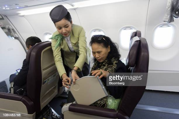 A flight attendant assists a passenger with a tray table in the business class cabin on board an Airbus SE A321 Neo aircraft operated by FLC Group...