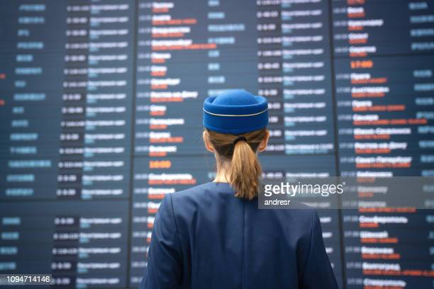 Flight attendant at the airport checking an arrival departure board