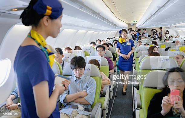 A flight attendant attends to passengers aboard the Airbus A330300 jetliner on June 14 2014 in Tokyo Japan Lowcost carrier Skymark Airlines...