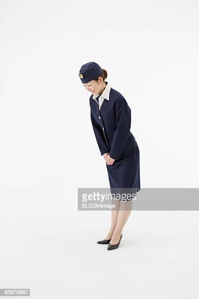 Flight attendant bowing, studio shot