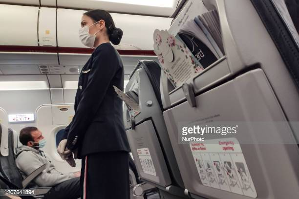 Flight attendant, cabin crew of Aegean Airlines wearing protective mask and gloves as a preventive measure against the spread of the COVID-19 at...
