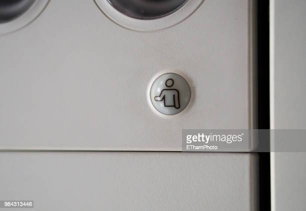 Flight attendant call button on ceiling inside passenger aircraft cabin