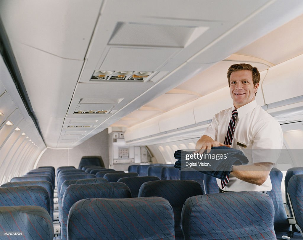 Flight Attendant Carrying a Blanket on a Plane : Stock Photo