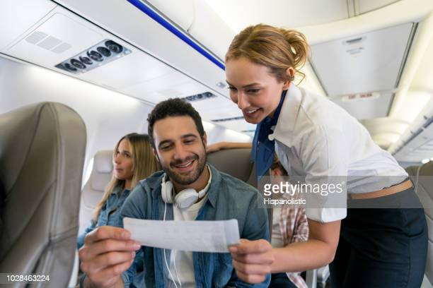 flight attendant checking a man's seat and her boarding pass - crew stock pictures, royalty-free photos & images