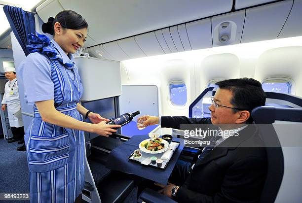 A flight attendant demonstrates All Nippon Airways Co's new branded service 'Inspiration of Japan' inside the business class cabin of a Boeing...